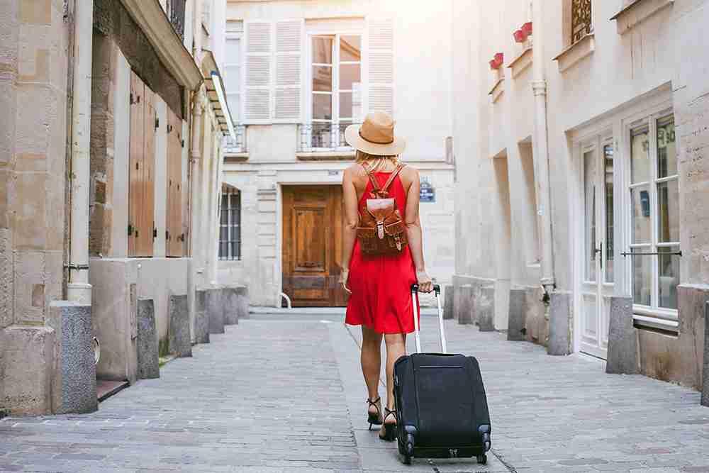 traveler walks to hotel with suitcase in Marais in paris